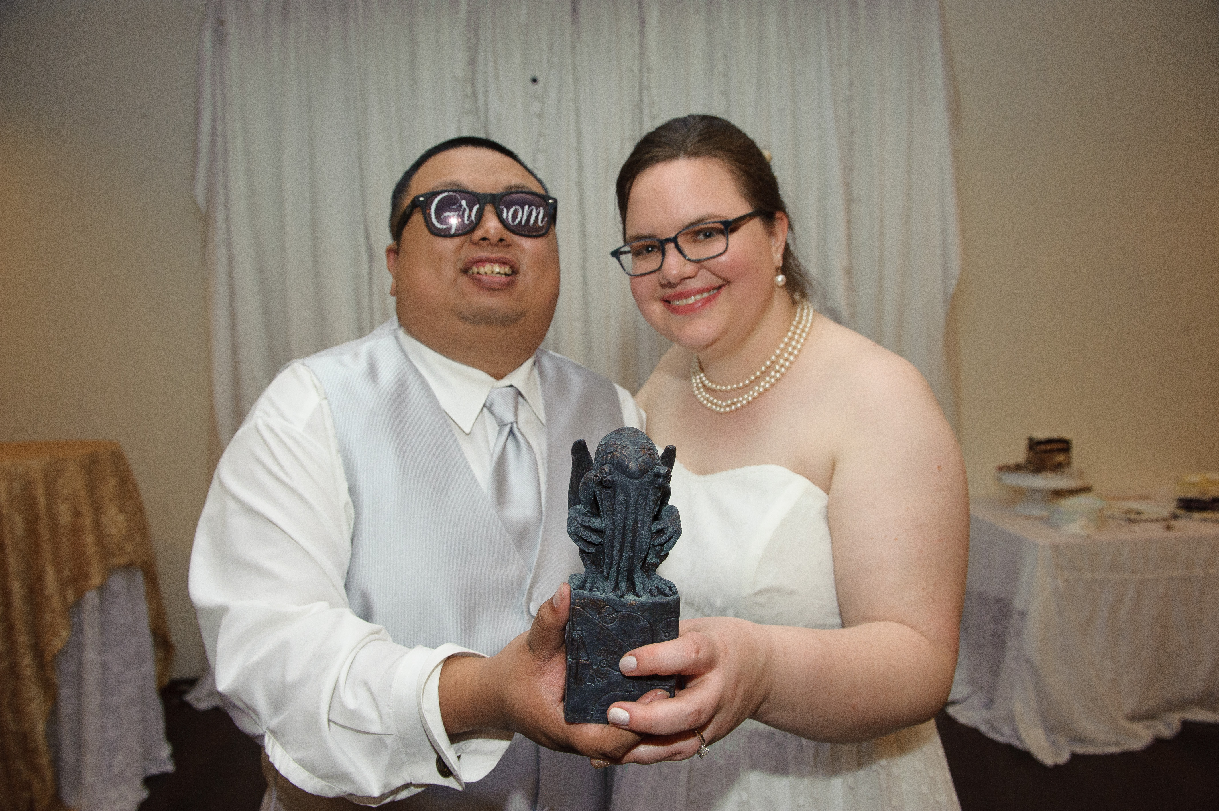 Megan and Aser hold out a Cthulhu statue after their wedding.
